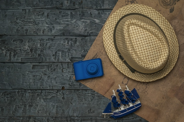 A hat, a model ship, and a camera on a piece of old paper on a wooden table. the concept of travel planning.