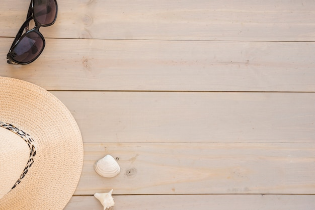 Шляпа возле ракушки и солнцезащитные очки