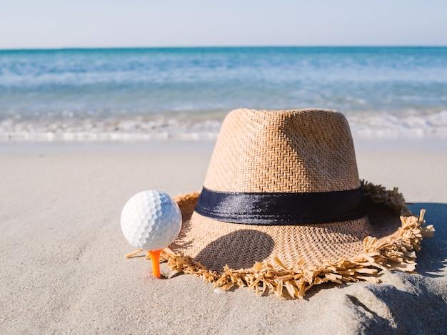 Шапка на песчаном пляже мяч для гольфа на вышитой футболке, на фоне моря.