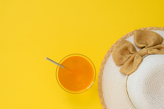 Hat and orange drink in bowl with cocktail straw on yellow background. the concept of summer vacation. flat lay. the view from the top.