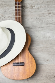 Hat over the wooden guitar against wooden plank backdrop