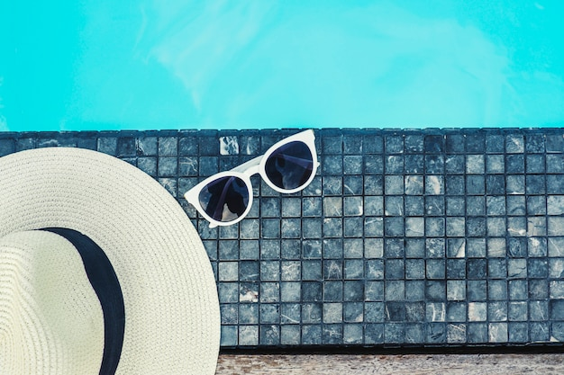 Hat and sunglass on luxury swimming pool tropical beach resort