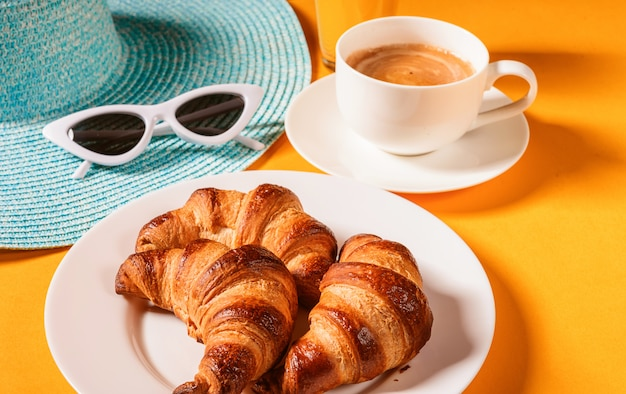 Hat, sunglasses croissant with a cup of coffee and a glass of orange juice on a yellow table in the sun