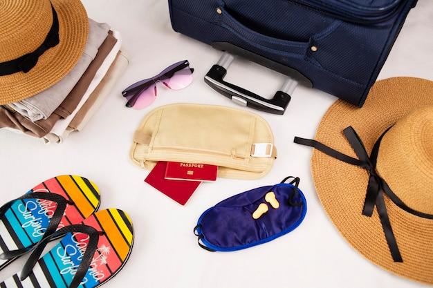 帽子サングラスフリップフロップとビーチアクセサリー荷物旅行アイテムスーツケースと帽子休暇や旅行の準備