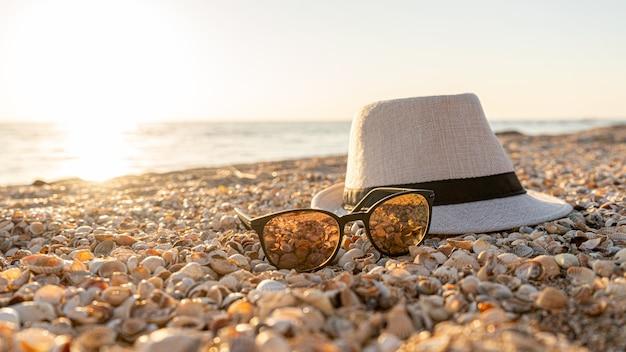 Шляпа, солнцезащитные очки на пляже с ракушкой на закате