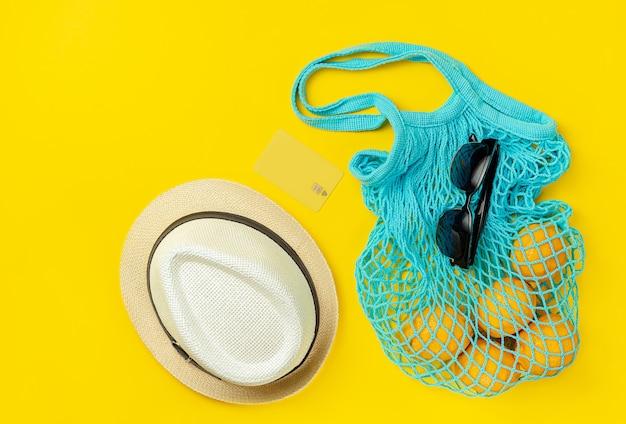 Шляпа, солнцезащитные очки, многоразовая сумка с лимонами и кредитной картой на желтом летнем фоне. концепция покупок в интернете