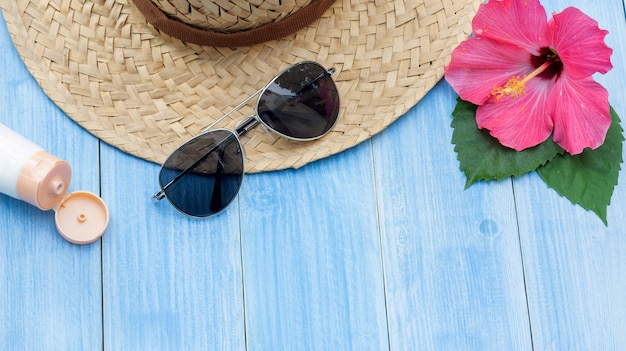 Hat, sunglasses, sunblock and chinese rose flower on a blue wooden table.