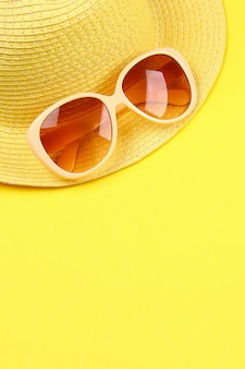 Hat, sunglasses on a yellow background.
