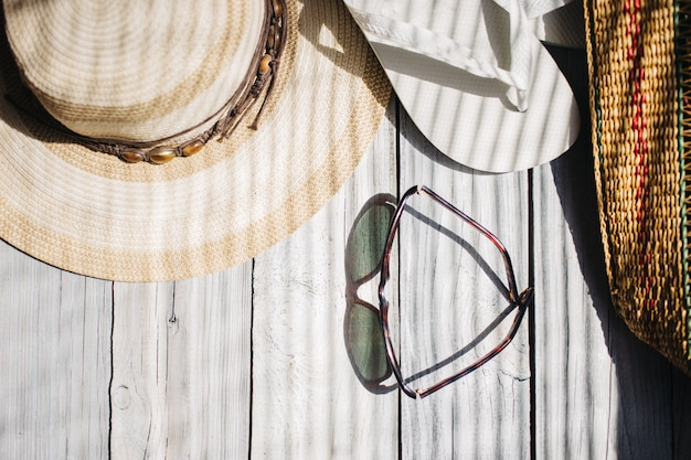 A hat, white flip flops, sunglasses, a beach bag on the white wooden background