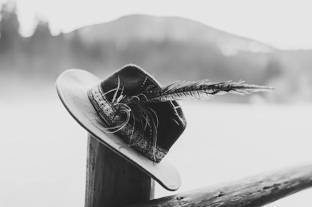 木製のフェンスに手作りの羽を持つ帽子。閉じる。黒と白の写真。