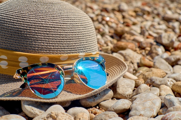 Hat with sunglasses on a pebble beach