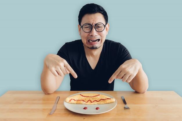 증오와 울고 아시아 남자는 오믈렛의 집에서 만든 아침 식사 세트를 먹고있다.