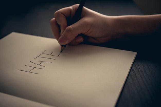 Concetto di odio - mano che scrive odio sul libro