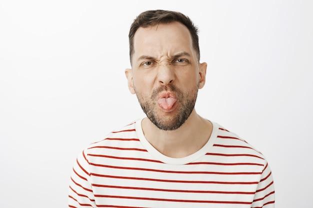 Ненавижу заниматься домашними делами. портрет недовольного непослушного мужа с щетиной, хмуриться и высунуть язык, будучи грубым и спорящим с ребенком