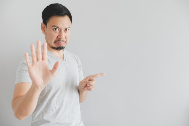 Hate face of man in grey t-shirt with hand point on empty space.