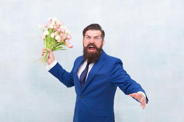 휴일을 싫어합니다. 여성의 날. 3월 8일. 꽃을 든 화난 수염 난 남자. 봄을 축하합니다. 날짜 실패. 튤립 꽃다발을 들고 짜증난 공격적인 수염 난 남자. 실망된 개념입니다. 실패한 날짜입니다.