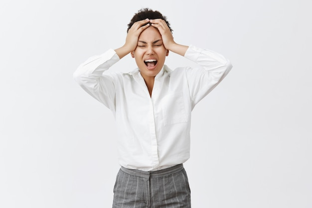 Hate mondays. unhappy bothered and distressed young determined businesswoman in formal outfit, yelling from stress and unpleasant feelings in soul, holding hands on head, tired and exhausted