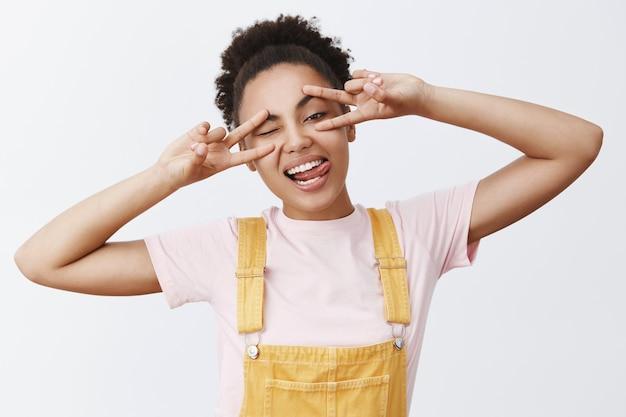 Le regole dell'odio vivono come vogliono. giovane ragazza africana dai capelli ricci felice e attraente spensierata con l'acconciatura del panino che mostra segni di pace sugli occhi, sporgendo gioiosamente la lingua sopra il muro grigio, divertendosi