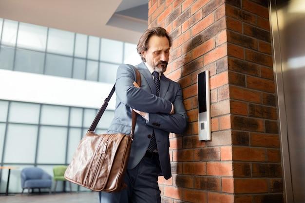 Ненавижу ждать. бородатый бизнесмен в сером костюме, ненавидящий ожидание возле лифта