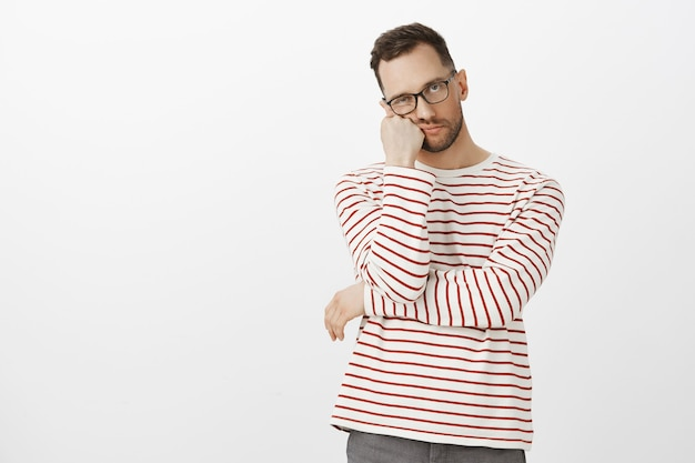 Hate waiting in queues. portrait of annoyed tired handsome guy with bristle in black eyewear, leaning face on hand and looking indifferent, standing bored over gray wall