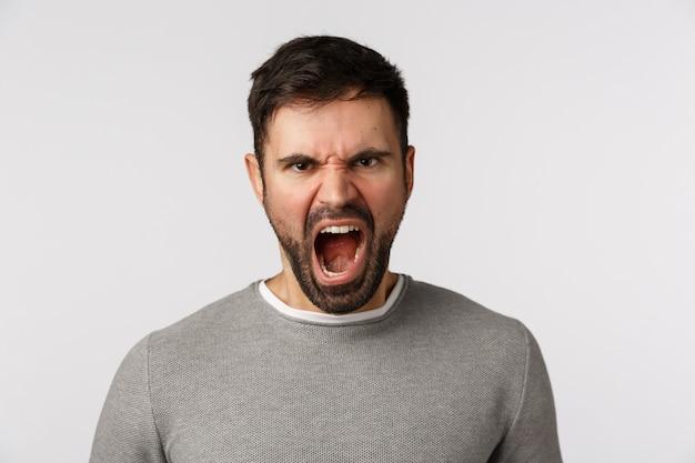 Ненавистный и бешеный сердитый кричащий бородатый человек со страшной гримасой, хмурым выражением презрения и презрения, жалуется на злобу, яростный крик, возмущенный стоя