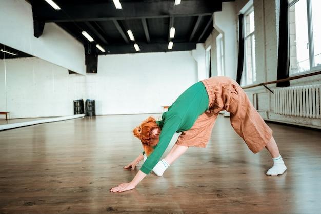 ハタヨガ。ハタヨガをしている緑のタートルネックを身に着けている美しいスリムなヨガのコーチ