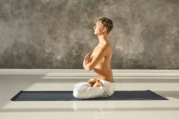 Hatha yoga, zen, spirituality, meditation and relaxation concept. portrait of peaceful concentrated young male yogi sitting shirtless on mat with hands in namaste, meditating in lotus posture