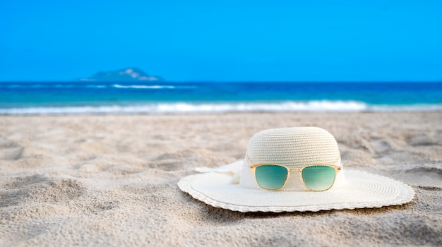 晴れた日には帽子と眼鏡が海の青い海のビーチにあります