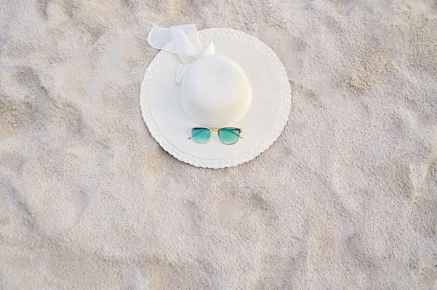 晴れた日には海の青い海のビーチに帽子とメガネが置かれます