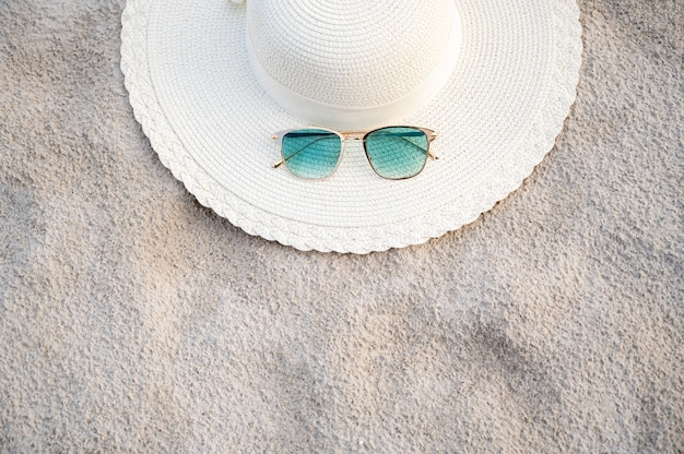 Hats and glasses are located on the sea blue sea beaches on a clear day