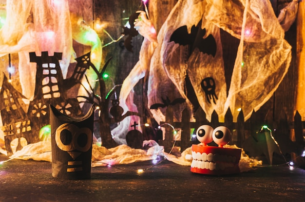 Haunted house with a grave and a scary tree on a wooden wall with a cobweb and led garland