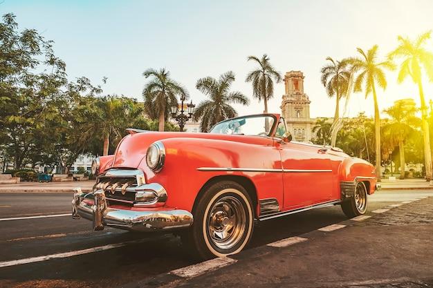 Гавана, куба. классический американский автомобиль на фоне пальм на ярком солнце вечером в гаване на фоне колониальной архитектуры