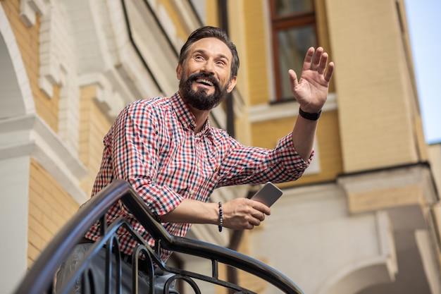 良い一日を過ごしてください。ポーチに立って隣人に挨拶するうれしそうなひげを生やした男のローアングル