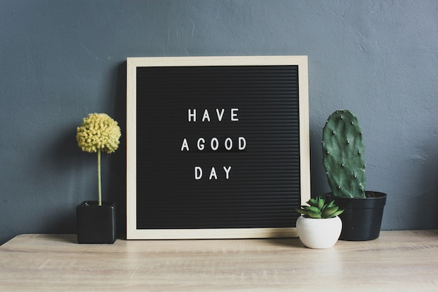 Цитата хорошего дня на доске с кактусом, сочными и декоративными растениями на деревянном столе
