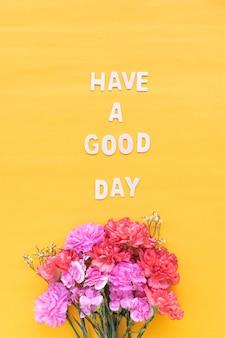 明るい黄色の背景に新鮮な花のカーネーションと良い一日の木の言葉を持って