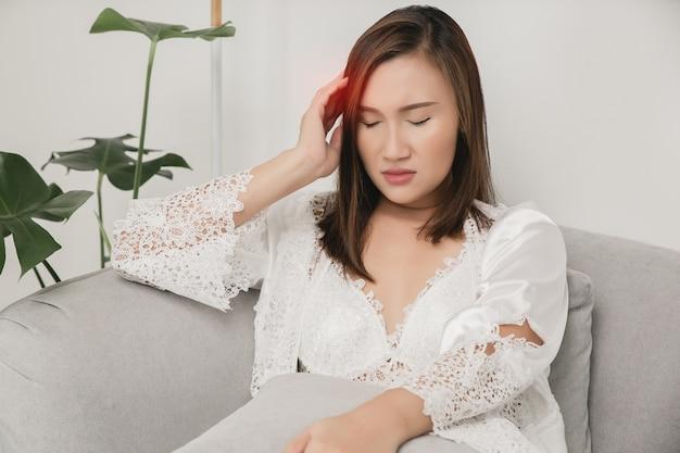 У женщин головная боль в атласной ночной рубашке и белом халате с цветочным кружевом на сером диване.