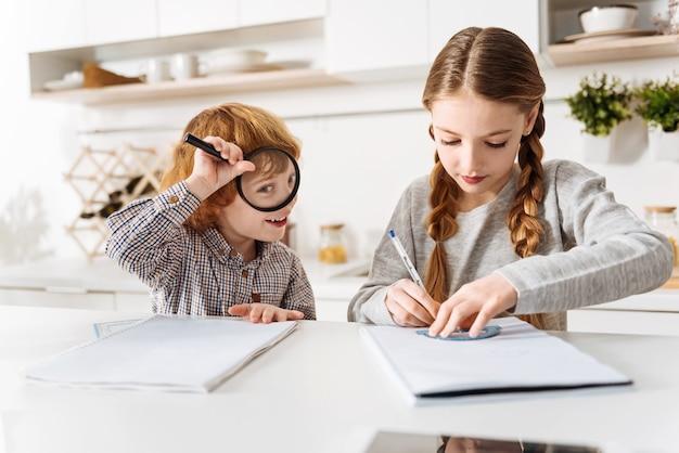 좀 즐기세요. 그의 여동생이 수학 수업을 위해 그녀의 집 과제를 시도하는 동안 돋보기를 가지고 노는 재미있는 활성 생강 소년