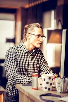 Взглянуть. внимательный фрилансер смотрит на свой компьютер во время создания задачи
