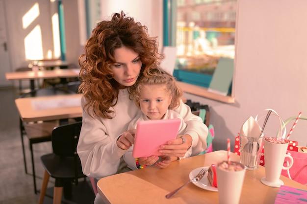 보세요. 뉴스를 읽는 동안 그녀의 가제트 화면을 응시하는 곱슬 머리를 가진 집중된 여자