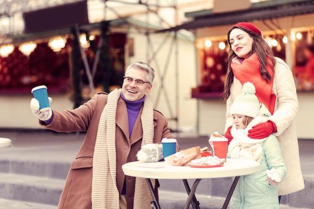 보세요. 테이블에 서서 카카오와 과자를 먹는 감정적 인 소녀