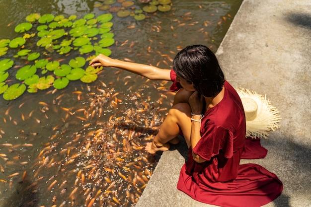 보세요. 수영장 근처에 앉아 물을 바라보며 잠시 쉬는 편안한 소녀