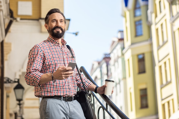 良い一日を。仕事に行く間彼のスマートフォンを使用して陽気なひげを生やした男