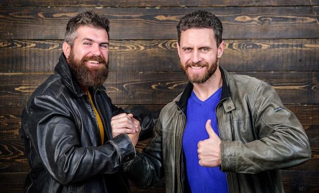 Согласился. брутальные бородатые мужчины в кожаных куртках обмениваются рукопожатием. крепкое рукопожатие. дружба жестоких парней. утвержденная коммерческая сделка. значение жеста рукопожатия. рукопожатие символ успешной сделки.