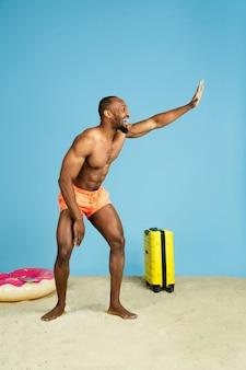 Divertiti. felice giovane uomo in appoggio con anello da spiaggia come una ciambella e borsa su sfondo blu studio. concetto di emozioni umane, espressione facciale, vacanze estive o fine settimana. freddo, estate, mare, oceano.