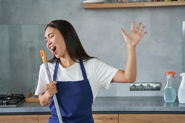 Веселиться. портрет радостной молодой женщины, уборщицы, притворяющейся поющей, держащей метлу во время уборки пола, занимающейся домашними делами. работа по дому и концепция ведения домашнего хозяйства