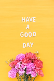 Have a good day  wooden word  with fresh flowers carnations on bright yellow background