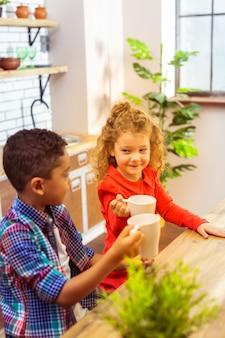 아이디어가 있습니다. 쾌활한 아이들이 부엌에 있고 컵을 만질 것입니다.