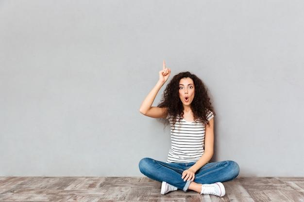 Есть идея! милая женщина в повседневной одежде, сидя со скрещенными ногами на полу, показывает указательным пальцем вверх, что означает эврика над серой стеной