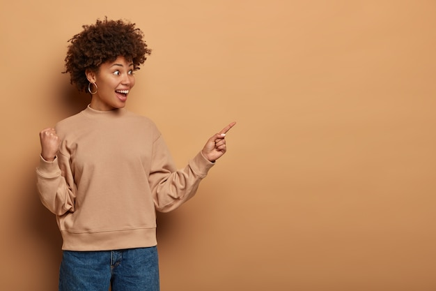 Have you seen it. joyful surprised ethnic girl shows way to awesome new event or promo banner, smiles happily and clenches fist, feels triumph, glad to reach desirable item, isolated on brown wall
