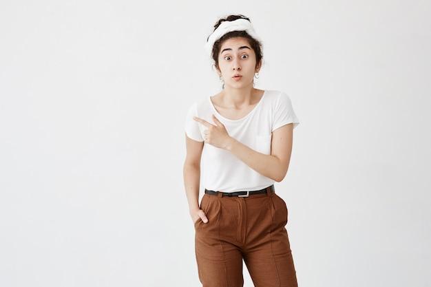 見た?人差し指を横向きにして、白い壁に何かを示す完全な不信感を見つめて、感情的な驚いた若い黒髪の女性の屋内ショット